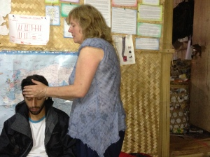 Night Hike casualty: A volunteer tries Reiki on Doc Mexico, stricken with Dengue fever.